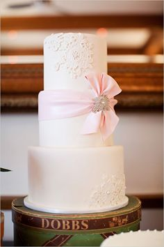 Soft pink wedding cake with lace floral details and a pink bow - so romantic