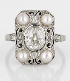 An art deco diamond and cultured pearl ring, circa 1925  centering an old oval-cut diamond accented by cultured pearls, old mine and single-cut diamonds; center diamond weighing approximately: 0.70 carat; mounted in eighteen karat white gold