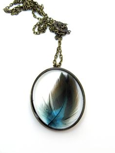 Encased in jewelers grade resin is a lovely teal color feather! It is encased in an oval shape antique bronze tone open back bezel. It would make a