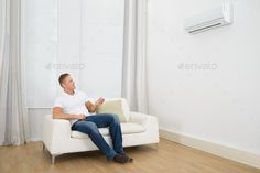 Man sitting on sofa operating air conditioner with remote control. http://photodune.net/item/man-adjusting-the-temperature-of-air-conditioner/10284287
