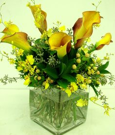 This is a cube vase floral arrangement that features mango miniature calla lilies with accents of yellow oncidium orchids. See our entire selection at www.starflor.com.  To purchase any of our floral selections, as gifts or décor, please call us at 800.520.8999 or visit our e-commerce portal at www.Starbrightnyc.com. This composition of flowers is generally available for same day delivery in New York City (NYC). SQ059