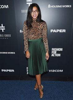 Hannah Bronfman wears a leopard-print sweater, green pleated midi skirt, tortoiseshell glasses, and metallic heels