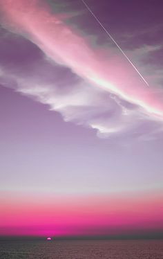 Beautiful Purple and Pink Sunset over ocean with airplane tracer in the sky