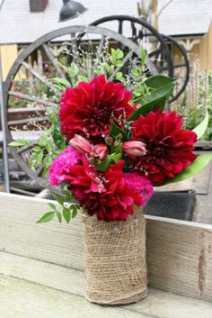 Red and pink summer flowers in burlap wrapped Mason jar are perfect small centerpiece for a rustic or western themed wedding. Centerpieces and  decor from Seasonal Celebrations. http://www.seasonalcelebrations.com
