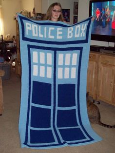 Mom made this for me in about two weeks from just a picture on a grid chart.  My mom is awesome.  And now my cat is trying to steal it.  I look at the colors as the TARDIS starting her phase program.
