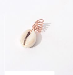 """The cowrie shell has been interpreted to be a symbol of power, prosperity and wealth. Many uses of the cowrie shell has grown as a statement of style! No matter how you interpret the meaning of a cowrie shell it is a """"must"""" have for those with locs and/or natural hair!The Cowrie Shell Collection is available with copper, silver or gold wire.*All pieces are handmade with love*"""