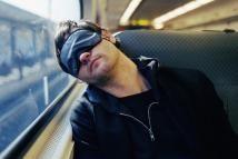man sleeping on train with eye mask - Sean De Burca/The Image Bank/Getty Images