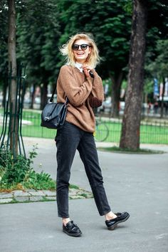 White blouse, brown studded sweater, black mom jeans, loafers, and a shoulder…