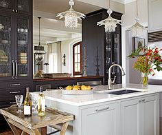 Seeded-glass doors are a sophisticated addition to the two dark-stained, armoirelike cabinets that flank the pass-through. Sparkling glass pendants add a delicate, feminine touch to the kitchen full of earthy elements./