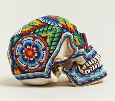 beaded sugar skull    this is a GENUINE HUMAN SKULL.  The Huichol tribe in the Sierra Madre mountains make these by pouring wax on the skull for preservation, then beading in traditional patterns and designs.    Gruesome and awesome.