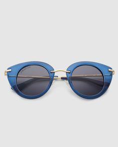Gafas de sol con montura ojo de gato de color azul y puente y varillas de metal dorado.