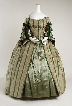 1858-63 Convertible Dress. This view is without the berthe (Shawl-like shoulder capelet) that would make this a day dress. Once the berthe is removed it becomes a dinner, or evening dress.
