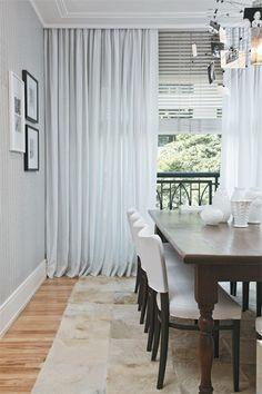 """""""O modelo de madeira dosa a luz e também serve de anteparo para proteger os tecidos e os móveis da sala"""", afirma Cris. Ambas as peças são brancas. """"Optei pelo linho pré-encolhido na cortina porque pode ser lavado em casa"""", diz. Com pregas americanas e barra de 20 cm dupla, a cortina de linho corre em trilho escondido no cortineiro. A persiana de madeira tem acionamento automatizado."""