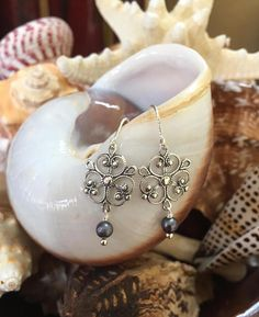 These beautiful earrings are layered with detailed Sterling Silver filigree and natural pearls. The ear hooks have a pretty rope detail with a lightweight feel and lovely movement. Measures: 1.50 inches from the top of ear hook to bottom of earring.  I use only top quality beads and lead/chromium free leather in my work.  Thanks for visiting...