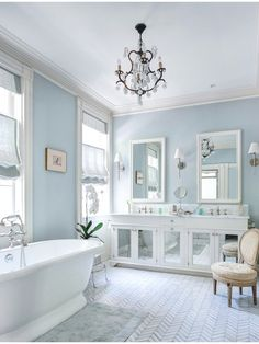 Soft sky blue walls embrace white cabinetry and large pedestal tub in this bathroom, with chevron pattern tile flooring.