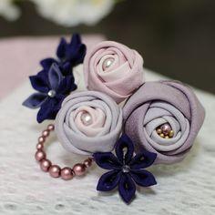 正絹の布を使用したつまみ細工のコームです。上品な紫とモーブピンクの玉バラです。シックな色ですので、年代問わずお使いいただけると思います。ビーズはチェコガラスパールになります。ボリュームのある和装のアップスタイルにいかがでしょうか。横幅:約9センチコームの大きさ:約5.5センチ(15本足)