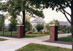 Love the way ornamental fence looks when paired with brick pillars.