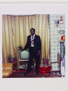Neil Kenlock, 'Untitled [A well fully clad man photographed standing by his television in Stockwell, South London]', Museum no. © Neil Kenlock/ Victoria and Albert Museum, London. Supported by the National Lottery through the Heritage Lottery Fund.