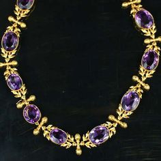 A late 19th century amethyst necklace and earring suite, circa 1890, the graduated row of oval amethysts each mounted within a rubover collet with millegrain detailing, set alternately with stylised foliate spacers each with a central baton capped by bud terminals, the earpendants en suite, length of necklace 41.0cm., length of earpendants 3.0cm. (earpendants not illustrated)