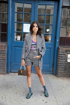 Leandra Medine of Man Repeller pairs green loafers with a shorts suit, striped shirt, and glitter socks