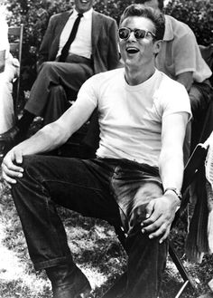 "James Dean wore his t-shirt without anything covering it in his movie ""Rebel Without A Cause"" Now, due to the movie's theme, the t-shirt plus the denim jeans were a symbol for youth rebellion and it was considered cool and finally accepted in the mid 50's."
