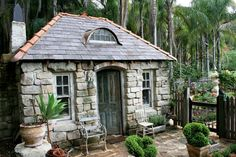 This is a potting shed! It took the owner 4 years to build from solid sandstone and vintage materials. It even has a working fireplace! Adjacent is a beautiful walled potager. Palm trees give clue to its location. Australia - not France. See more photos and learn more about the garden at the website.