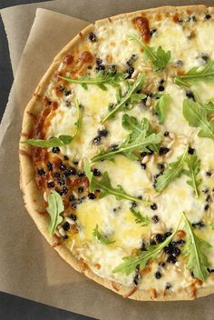 Mozzarella pizza with pine nuts, currants & arugula.... interesting combination must try