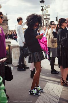 Julia Sarr-Jamois in a black sweater, black pleated leather skirt, and NIKE sneakers.