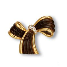 AN 18K GOLD, WOOD AND DIAMOND CLIP BROOCH, BY VAN CLEEF & ARPELS    Designed as carved wood ribbon to the gold trims, enhanced by brilliant-cut diamond detail, mounted in 18k gold, 5.9 cm wide, with French assay mark for gold, in a Van Cleef & Arpels blue suede pouch    Signed Van Cleef & Arpels, no. B1302B1