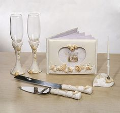 The Beach Bridal Accessories Set will make a perfect addition to your beautiful beach theme or destination wedding.  Each piece is embellished with beautiful seashells and pearls.  Set includes a guest book, pen set, toasting flutes and cake server set.