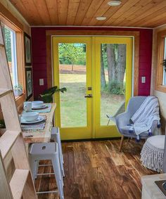 The interior has several pops of color throughout, including the yellow door, a red accent wall around the door, teal green in the lofts, and green and mustard yellow in the kitchen.