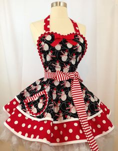 Come in from the cold and enjoy snowmen in your kitchen! This Sweetheart Apron is an adorable 2-tier circle skirt pinup design that is very feminine, flirty, and fun! The main fabric features a snowmen in red, black and white with swirling lines. The lower skirt is an eye-popping red and white polka dot, while the waist ties are candy cane striped red and white. The bodice has a sweetheart neckline trimmed in white bias and accented with lipstick red ric rack and a big red bow. The bodice…