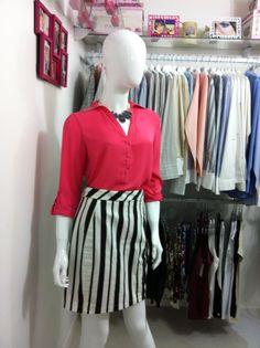 Combinar uma camisa de cor forte, como o rosa pink, com o listrado P é uma forma de deixar o visual mais vivo, aproveitando as tendências da estação.  Camisa: R$ 119,00 Saia: R$ 99,90