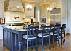 beautiful kitchen with blue island and chairs