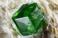 This type of garnet, known as a demantoid, gets its color from a dash of chromium. Many demantoids have feathery needle crystals of asbestos growing in them, known as horsetails.
