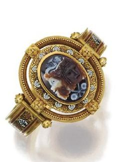 ARCHAEOLOGICAL-REVIVAL GOLD, HARDSTONE CAMEO AND ENAMEL BANGLE-BRACELET, JOHN BROGDEN, CIRCA 1870. The center decorated with a sardonyx cameo carved with the head of Bacchus overlapping the profile of a satyr, a wine cup and grape clusters above, further decorated with a pattern of anthemion in black, white, brick-red and blue enamel, the cameo also framed by rope-twist and granulation accents, signed J.B.