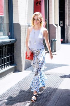 Sienna Miller wears a gray tank top, printed ruffle maxi skirt, orange Gucci bag, slide sandals, and mirrored sunglasses