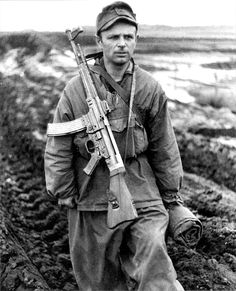 """Late in the war, a German soldier is carrying an StG-43/44 """"Sturmgewehr"""" assault rifle of advanced design."""