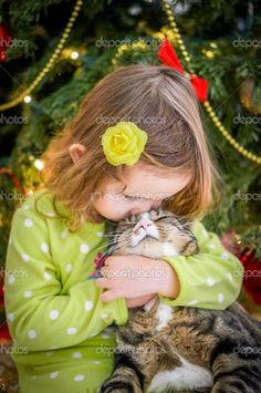 linda niña con vestido verde está besando a un gato cerca de árbol de Navidad - Imagen de stock: 37198889