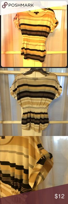 """Striped dress top Gold, silver, black & white striped dressy top. Cinched at waist & cute button detail on the sleeves. This shirt is so classy & elegant! No flaws & from a smoke free & pet free home!! 👍🏻also comes with an extra button! Fabric- 100% polyester. Approximate flat measurements: length 24"""" cinched waist 12"""" under cinched waist 19"""". Ask questions & offers always considered!! 😊 Attention Tops Blouses"""