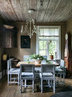 Gorgeous Scandinavian dining room with grey blue chairs, tall clock, built-in wood cabinet, and wide plank wood floors.