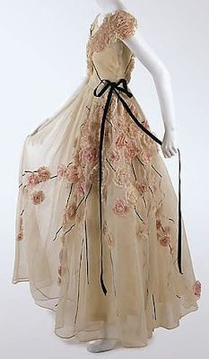 Lanvin 1937 Cream with a black ribbon at the waist and a waterfall of roses at the waist.