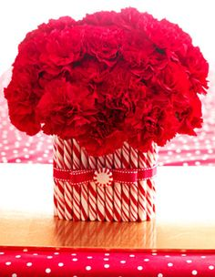 DIY Candy Cane Holiday Centerpiece: I'm not a huge carnation fan but I kinda love this...a lot and you could use those old fashioned candy sticks instead of candy canes