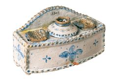 Inkstand | The Museum of the Shenandoah Valley John Bell, 1800 - 1880 ca.1825 This is the first documented tin-glazed ceramic object made in America. The stand has pierced holes to receive tiny receptacles for sand and ink. Bell's mark appears in raised lettering on the upright extension of the back. The town and date are incised in script on the back, as well. John Bell was the oldest child of potter Peter Bell Jr. He moved to Winchester in 1824.