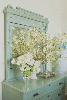 beautiful white flowers on a blue/green dresser
