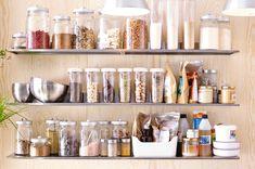 Tři nerezové nástěnné police IKEA s množstvím dóz na ukládání potravin.