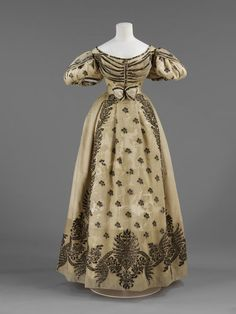 Silver-embroidered silk crepe over satin wedding gown with silver lace trim, French (Paris), 1828. Worn by the Honourable Frances Barrington for her marriage to William Legge, 4th Earl of Dartford. Worn with coordinating silver-embroidered white silk garters, and white silk slippers embroidered with cream.