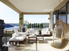 """Chic Sydney home with harbour views:The terrace off the formal living room offers spectacular Sydney harbour views. Minotti Alison Iroko **sofa** and **chaise** and Vittorio Bonacina Eureka **hanging cane chair**, all from [Dedece](http://www.dedece.com/ target=""""_blank""""). **Side tables** sourced in Morocco. **Sculpture** by Robert Klippel."""