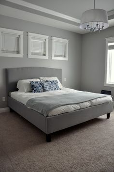 DIY Bed frame/headboard.  The grey upholstery and wall color (with white accents) would look good with our black/brown furniture