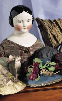 """22"""" German Porcelain Doll with Brown Eyes~~~old muslin stitch-jointed body with kid arms, sewn on striped stockings and leather boots, lovely gown of antique brown taffeta fabrics, antique undergarments. CONDITION: Generally excellent. COMMENTS: circa 1865. VALUE POINTS: Pink tinted complexion and brown eyes, original body."""